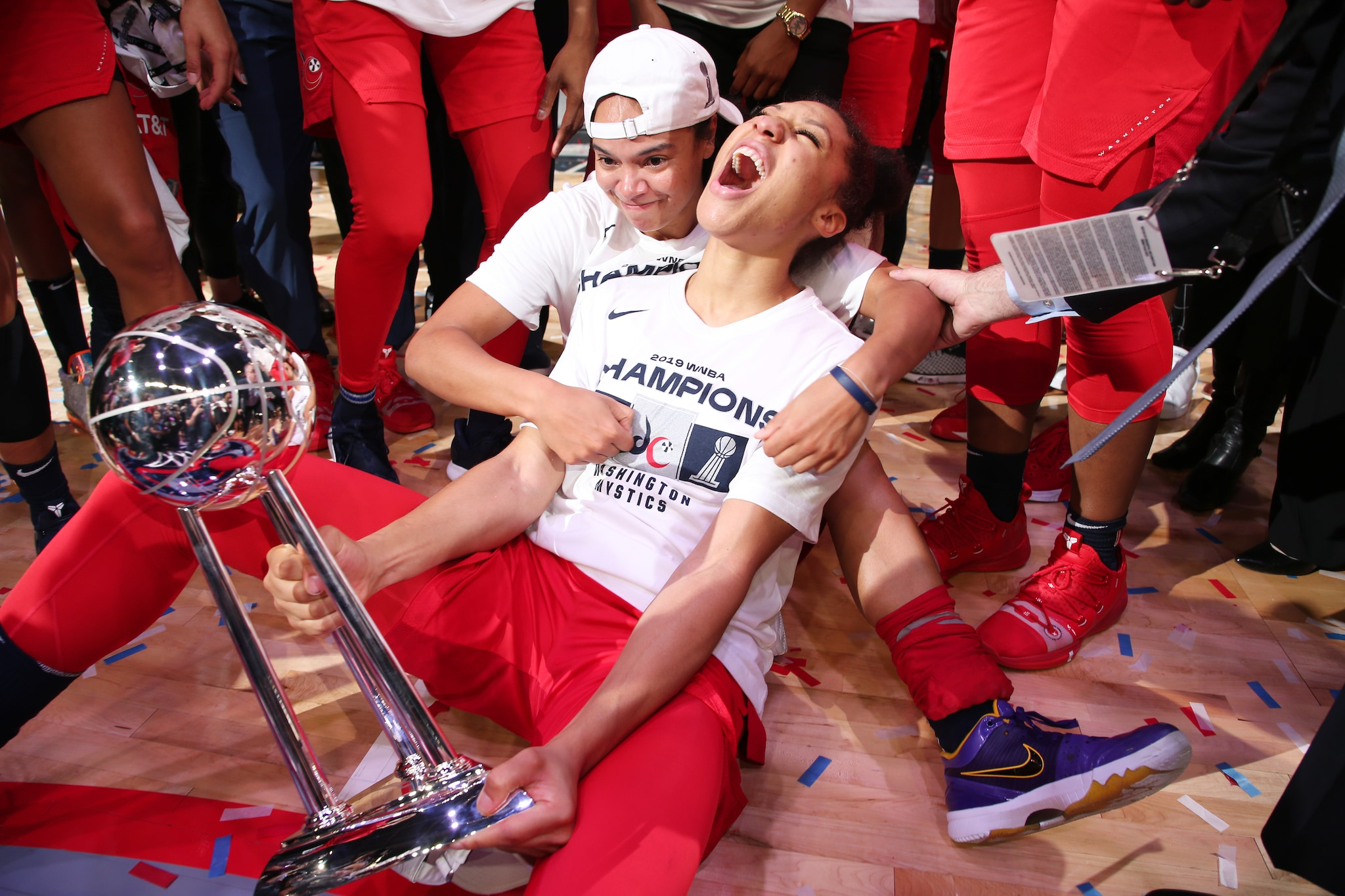 Aerial Powers and Kristi Toliver celebrate with the Mystics' trophy