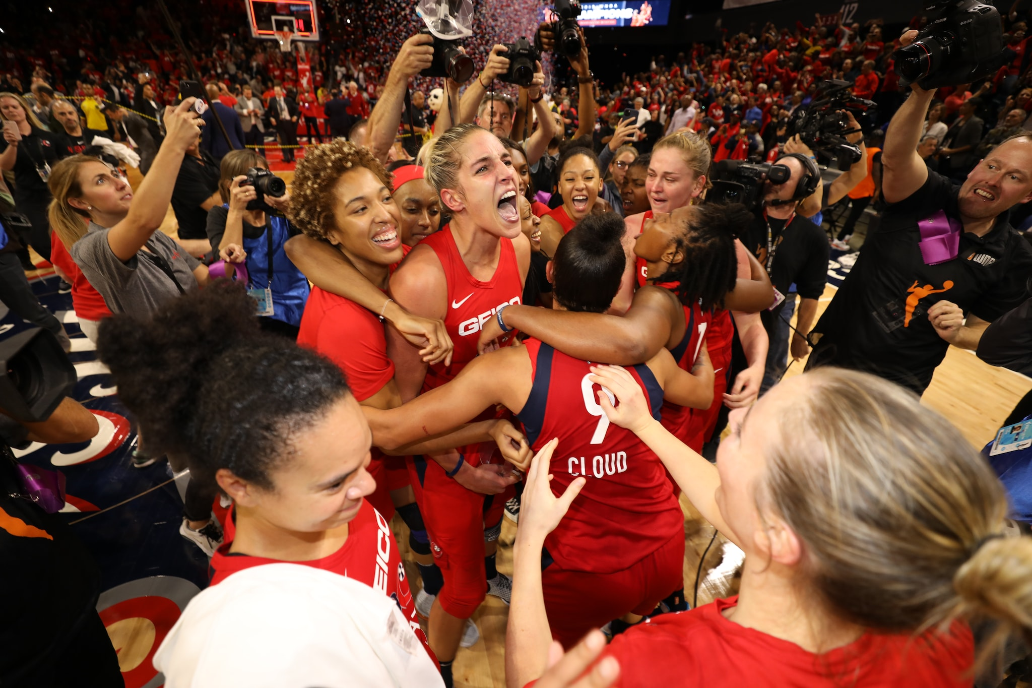 The Mystics celebrate on the court after the final buzzer sounds.