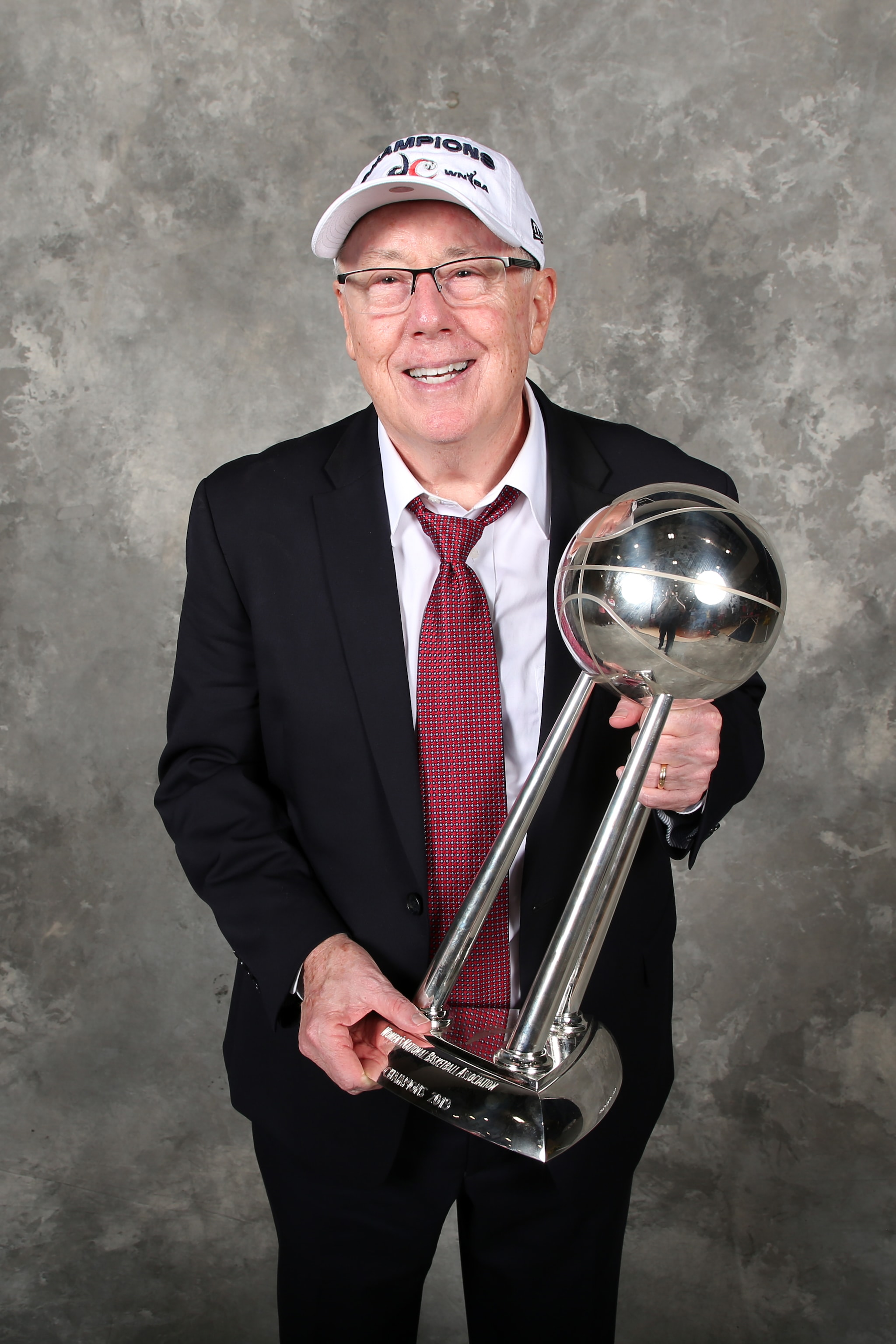 The winningest coach in WNBA history, Mike Thibault, poses with the WNBA Finals trophy.
