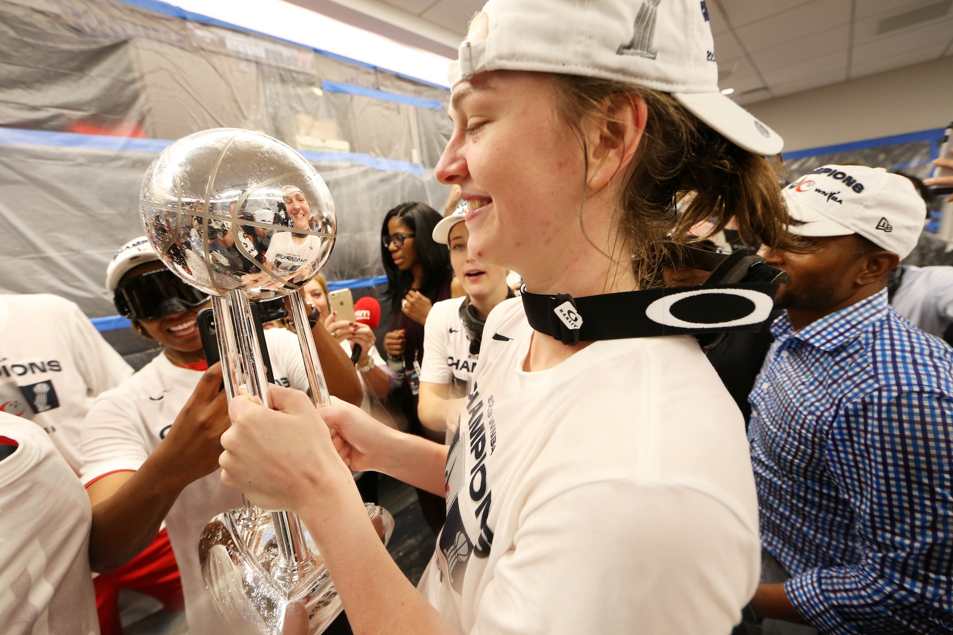 Emma Meesseman celebrates with the WNBA Finals trophy in the locker room.