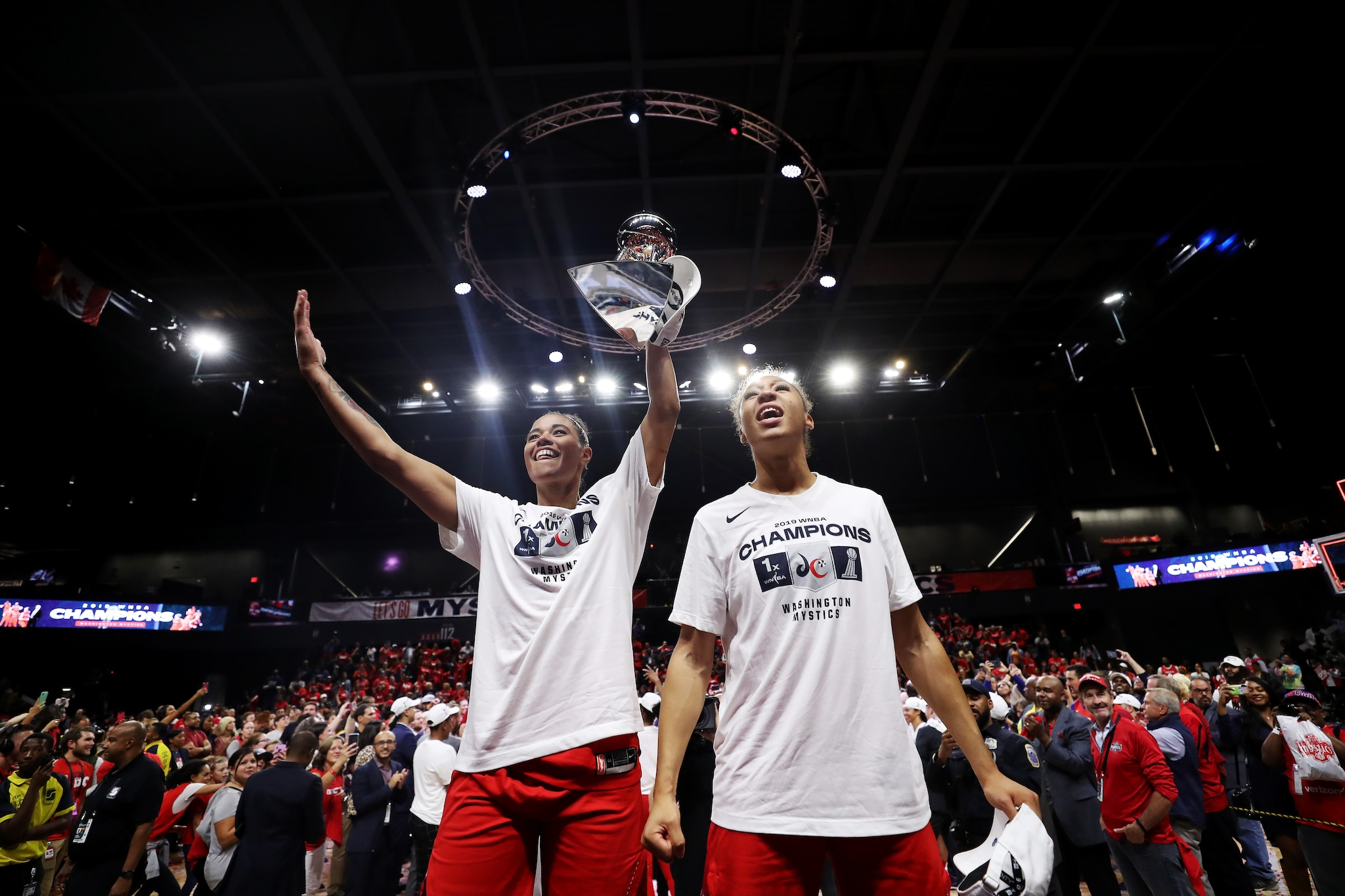 Natasha Cloud and Aerial Powers show off the WNBA Finals trophy to the crowd.