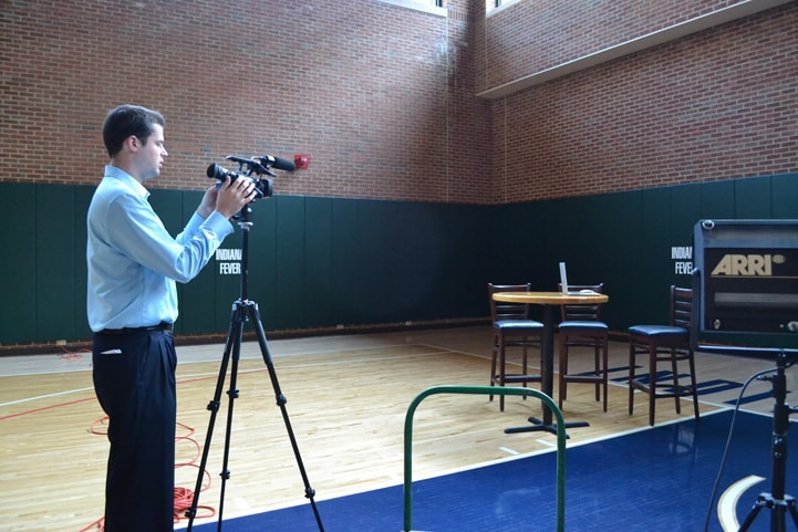 A web team staffer sets up an interview area with a camera and a table.