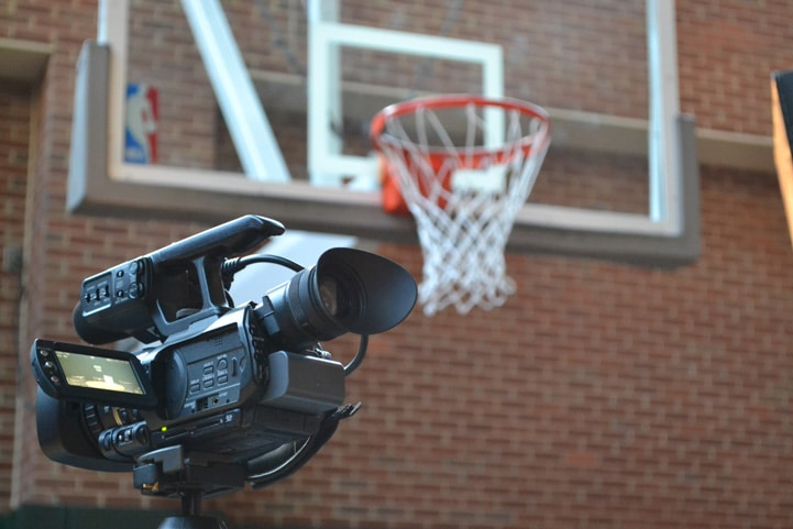 A video camera is set up with a basketball hoop hanging over it.