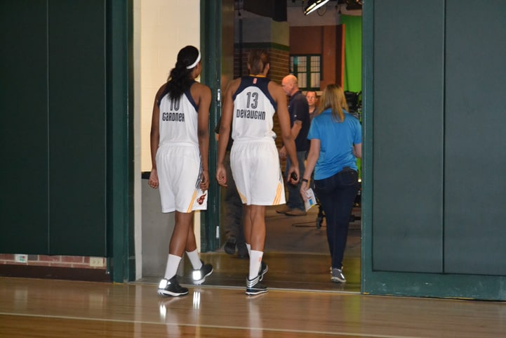 Chelsea Gardner (#10) and Alicia DeVaughn (#13) walking through a doorway on their way to media obligations.