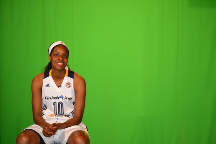 Chelsea Gardner (#10) smiles for a photo in front of a green screen.