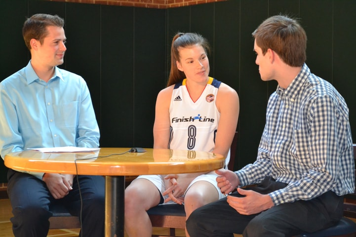 Maggie Lucas sitting at a table between two men interviewing her during media day.