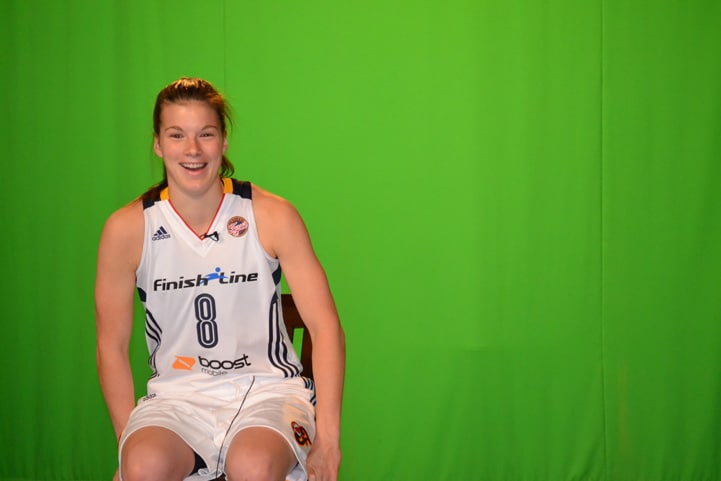 Maggie Lucas (#8) smiles in front of a green screen at Indiana Fever Media Day.