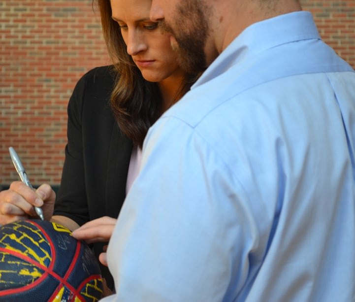 Head coach Stephanie White signs a blue, yellow and red Indiana Fever basketball with a silver Sharpie.