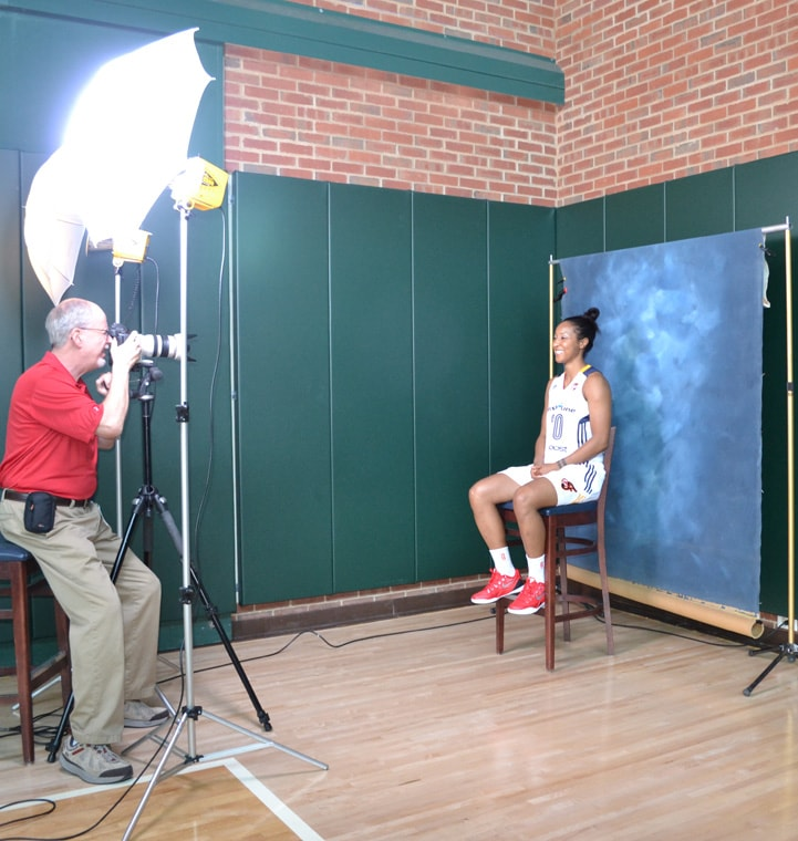 Briann January (#20) sits on a stool in front of a blue background for a photo at Indiana Fever Media Day.