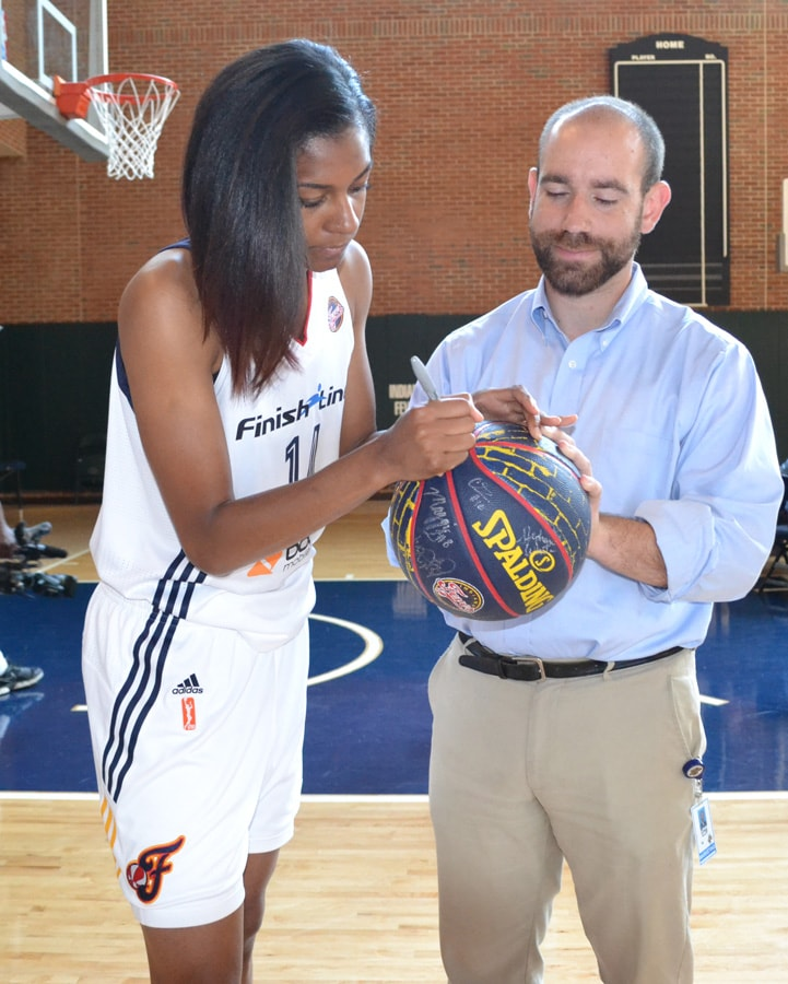 Briana Butler signs a Fever basketball at Indiana Fever Media Day.