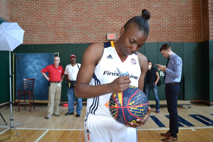Tyaunna Marshall signs a Fever basketball during Indiana Fever Media Day.