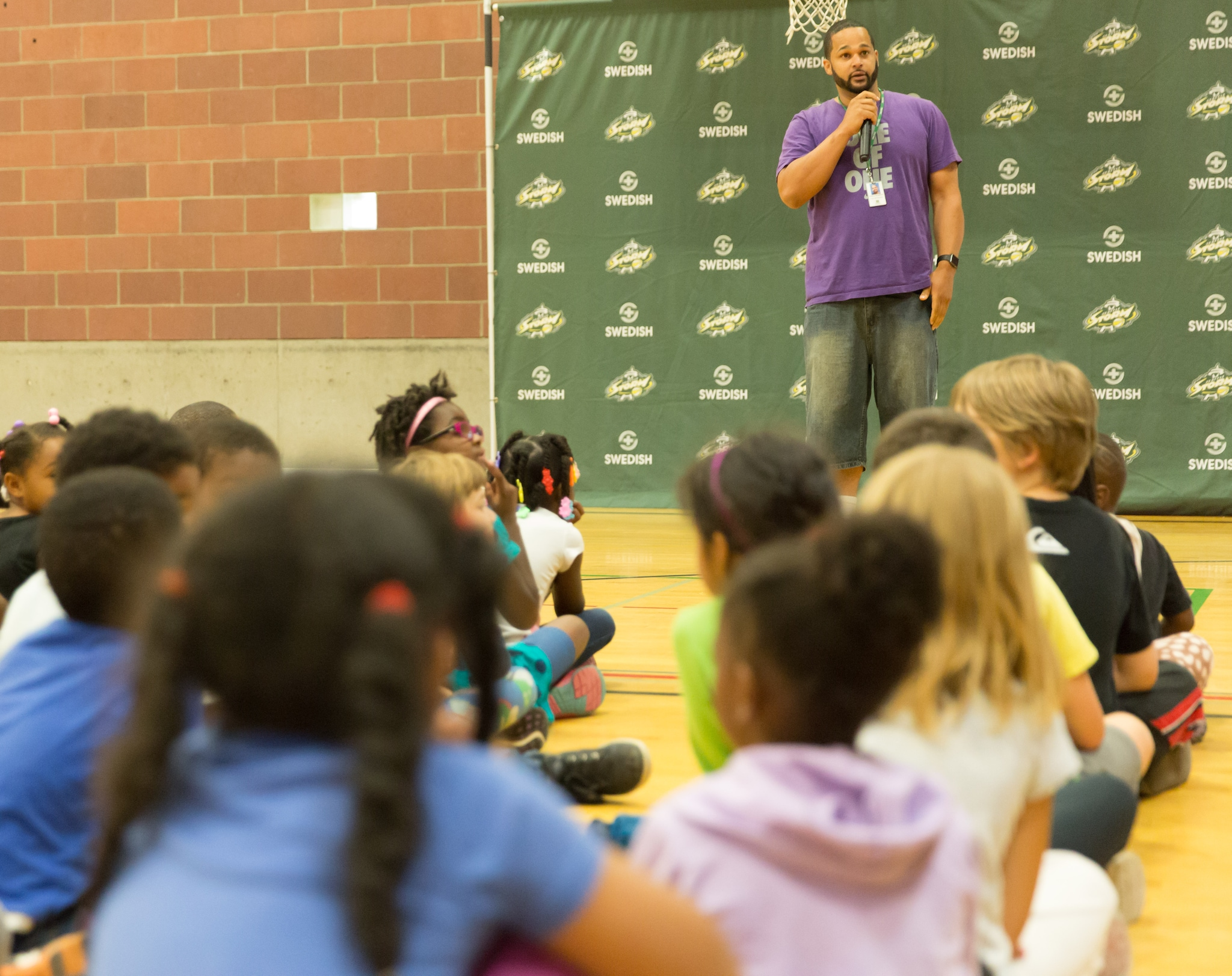 Andre Franklin, from the teen and young adult unit of Seattle Parks and Recreation, welcomes kids to the event. (Neil Enns/Storm Photos)
