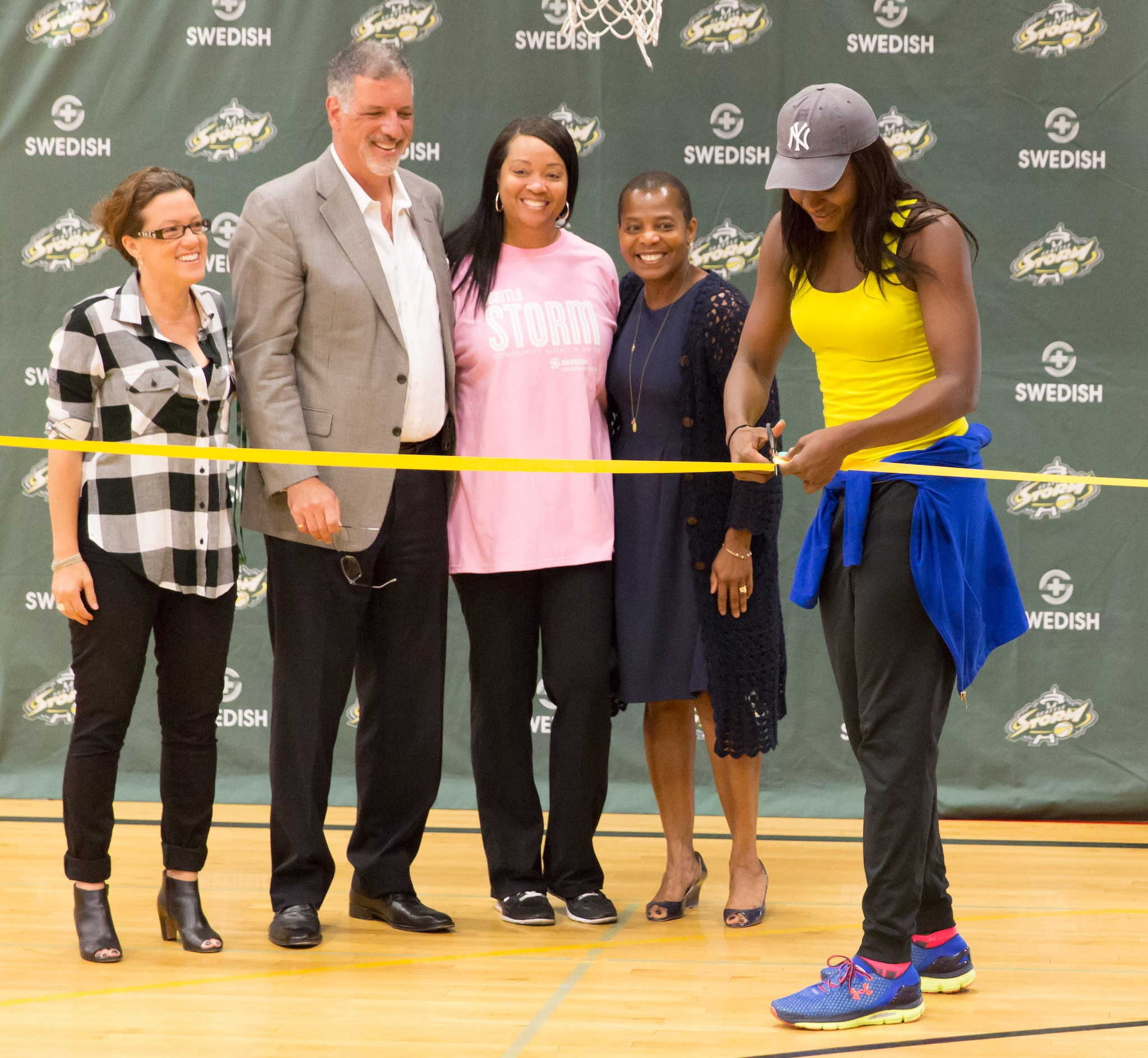 Seattle Storm forward Crystal Langhorne cuts the ribbon to officially open the new adjustable-height backboards for play. (Neil Enns/Storm Photos)