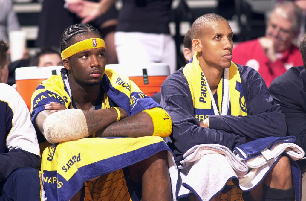 AUBURN HILLS, MI - MAY 26:  Jermaine O'Neal #7 (L) and Reggie Miller #31 of the Indiana Pacers sit on the bench during the 85-78 loss to the Detroit Pistons in game three of the Eastern Conference Finals during the 2004 NBA Playoffs on May 26, 2004 at the Palace of Auburn Hills, in Auburn Hills, Michigan.  NOTE TO USER: User expressly acknowledges and agrees that, by downloading and or using this photograph, User is consenting to the terms and conditions of the Getty Images License Agreement. Mandatory Copyright Notice: Copyright 2004 NBAE (Photo by Allen Einstein/NBAE via Getty Images)