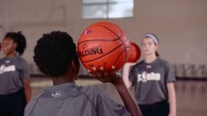 Watch WNBA player Tamera Young teach better ball control by working on one-handed passes and catches in the Stationary 2-Ball Passing Drill.